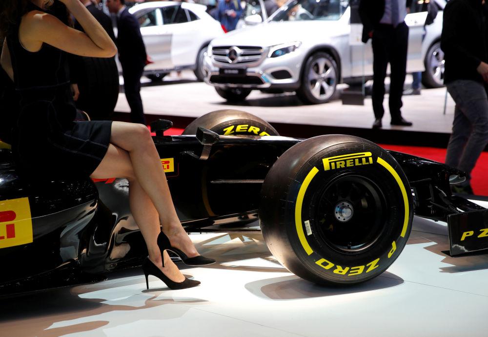 Модель у реплики болида Формулы-1 на стенде Pirelli на автосалоне Geneva International Motor Show 2018 в Женеве, Швейцария