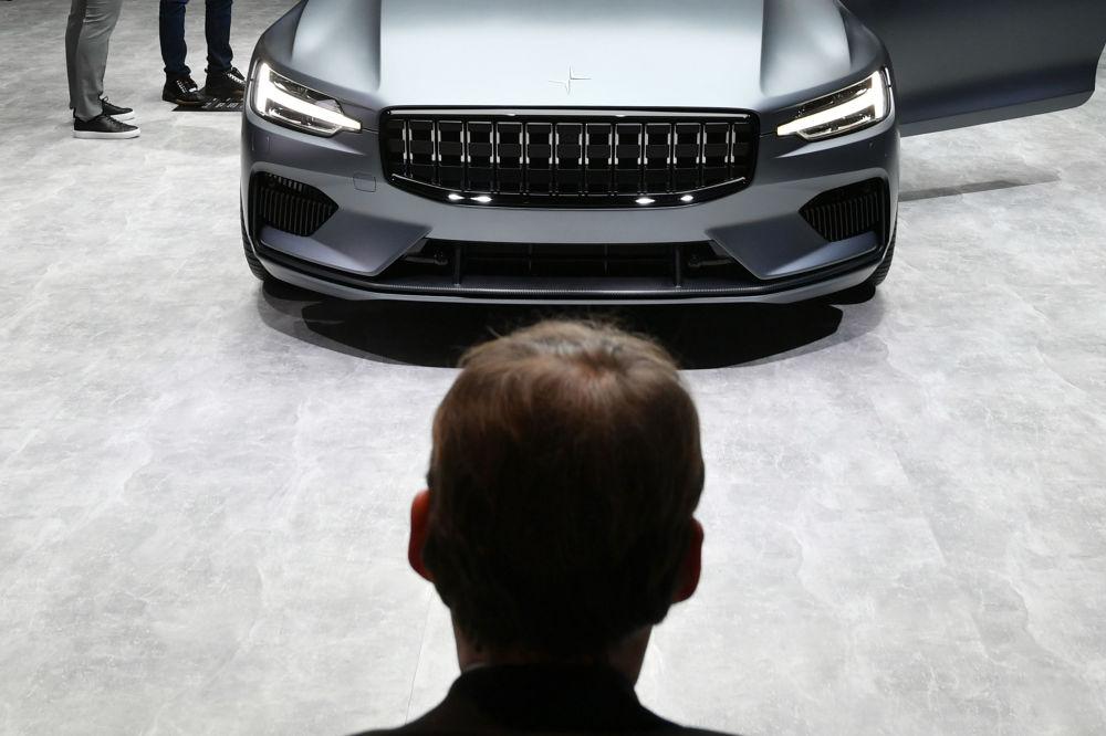 Посетитель у автомобиля Polestar 1 от бренда Volvo Car Group на автосалоне Geneva International Motor Show 2018 в Женеве, Швейцария