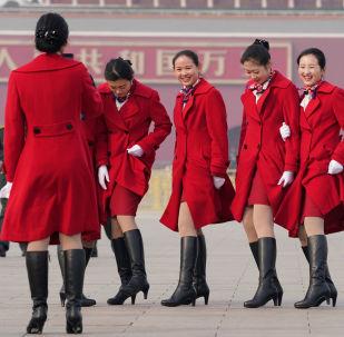 Девушки-хостес Всекитайского собрания народных представителей фотографируются на площади Тяньаньмэнь в Пекине, КНР
