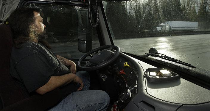 Водитель в кабине грузовика. Архивное фото