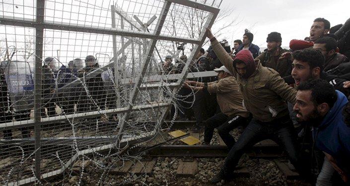 Migranti cenšas sagāzr nožogojumu protesta akcijas laikā. Foto no arhīva